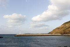 Jetty with brown mountain in deep blue ocean on cloudy blue sky Royalty Free Stock Photo