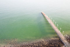Jetty on the coast reaches out to calm green sea Stock Images