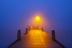 Jetty on a foggy morning at dawn. A jetty with a lamppost on a foggy morning at dawn Stock Photography