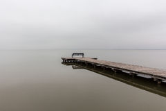 Jetty in foggy weather with bench, diagonal shot Royalty Free Stock Image
