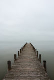 Jetty in foggy weather (vertical). Deserted jetty, pier in foggy weather, vertical shot stock photo