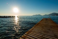 Jetty and island in sunset Royalty Free Stock Photos