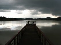 Jetty on Keonjhar lake. Black and white scenic view of lonely jetty on Keonjhar lake with cloudscape reflected on water, Orissa, India Stock Image