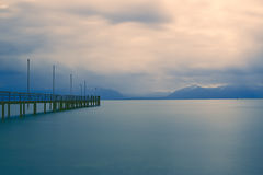 Jetty on lake Chiemsee, Germany. Shot taken with long exposure time on a foggy day stock image