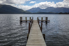 Jetty on a lake with mountain view Stock Image