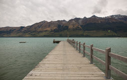 Jetty on a lake with mountain view Stock Photos