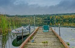Jetty on a lake with small boat royalty free stock image