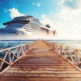 Jetty leading to the cruise ship ready to sail for a trip. Pier on the sea at sunset with cruise ship royalty free stock photography