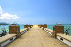 Jetty that leads to an tropical island. And sky Royalty Free Stock Photo
