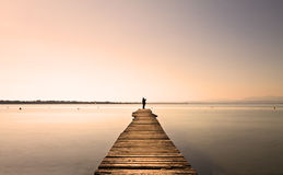 Jetty. Man standing on a small jetty, enjoying the  sunset over a lake Stock Images