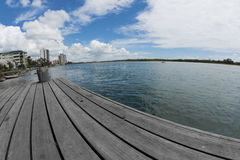 Jetty on Maroochy River. Long wooden planked jetty on Maroochy river at Maroochydore, Sunshine Coast, Queensland, Australia. Some highrise resort building on stock photos