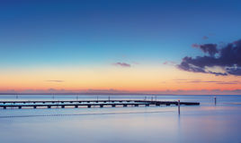 The jetty over the ocean at sunset Stock Image