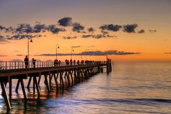 Jetty with people silhouette during sunset. With waving sea Royalty Free Stock Photo