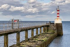 A small red and white lighthouse on the end of a jetty royalty free stock photography