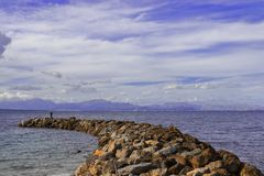 Jetty / pier of rocks with man fishing and mountain backdrop, mediterranean sea, mallorca, spain stock images