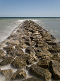 Jetty of Rocks to the Sea. Jetty of rocks leading into the sea. Photo taken with a long time of exposure Stock Photo