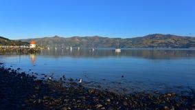Jetty and scenic bays of Akaroa, Banks Peninsula. In New Zealand Royalty Free Stock Photos