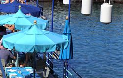Italy Sorrento - a jetty with blue sunshades. A jetty by the sea where people are dining under the shade of blue parasols stock photos
