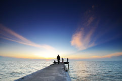 Jetty and silhouette of angler fishing during sunset at straits Stock Image