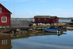 Jetty with Small Boat in Sweden. Jetty with a small motorboat and houses on the small island of Kallo-Knippla to the north of Goteborg in Sweden Royalty Free Stock Image