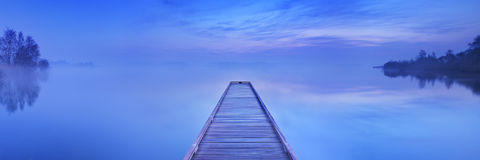 Jetty on a still lake at dawn in The Netherlands Royalty Free Stock Photography