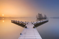 Jetty on a still lake on a foggy winter's morning Stock Image
