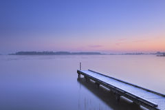 Jetty on a still lake in winter in The Netherlands Royalty Free Stock Image