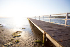 Jetty into the sun. A jetty at a lake at sunset Stock Image
