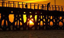 Jetty Sunset. A shot of a Jetty at Sunset with a man and child in silhouette Stock Photo