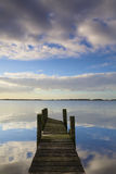 A jetty at sunset with reflection and sunshine Royalty Free Stock Image
