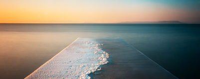 Jetty at sunset. Winter sunset over the sea - snow-covered pier, blurred sea and beautiful colors Royalty Free Stock Photo