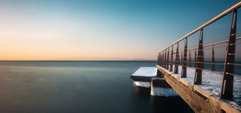 Jetty at sunset. Winter sunset over the sea - snow-covered pier, blurred sea and beautiful colors Royalty Free Stock Photography