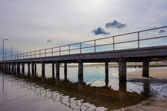 Jetty with Tide Out. A long wooden jetty with the tide out. Boats just visible in the background Stock Photo