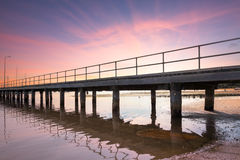 Jetty with Tide Out at Sunset. A long wooden jetty with the tide out at sunset. Boats just visible in the background Stock Photos