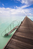 Jetty to the horizon. Endless jetty to the horizon; view to a turquoise sea and blue sky with white clouds Stock Photography
