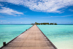 Jetty to the island. Jetty to a little tropical island in the turquoise indian ocean, maldives, way to a travel destination Stock Image