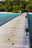 Jetty to a little tropical island in the turquoise i. Ndian ocean, maldives, way to a travel destination Royalty Free Stock Images