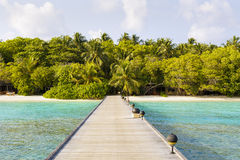 Jetty to a little tropical island in the turquoise indian ocean, maldives, way to a travel Royalty Free Stock Photos