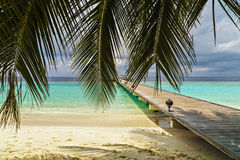 Jetty to a little tropical island in the turquoise. Indian ocean, maldives, way to a travel destination Stock Image