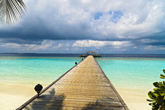 Jetty to a little tropical island. In the turquoise indian ocean, maldives, way to a travel destination Royalty Free Stock Photo