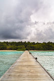 Jetty to a little tropical island. In the turquoise indian ocean, maldives, way to a travel destination Royalty Free Stock Photos
