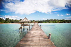 Jetty to a tropical beach. With blue sky background Royalty Free Stock Photo