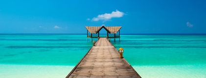 Jetty on a tropical beach. Into the ocean Stock Photography