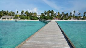 Jetty of a resort with palmtrees on the background. Jetty with turquoise lagoon and palmtrees at the back ground on a sunny day Stock Photo