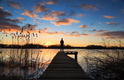 Jetty view. Man standing on a small jetty, enjoying the winter sunset over a lake Stock Image