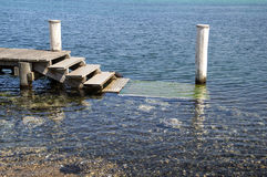 Jetty. On the water with four metal steps and landing Royalty Free Stock Photography