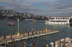 Jetty on the waterfront and floating ship on the Bosphorus on a sunny day in Istanbul, Turkey. Toned image. Stock Image