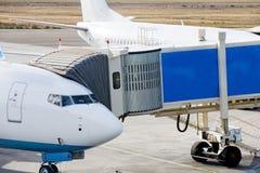 Jetway tjänas som till passagerareflygplanet på flygplatsen close upp Förberedelse för avvikelse som ombord stiger ombord passage Arkivfoton