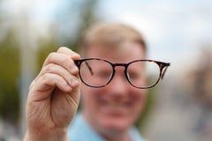 Jetzt kann ich Sie gut sehen Hübscher junger Mann, der Gläser hält und durch sie schaut Stockbilder