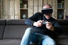 Jeu adulte d'homme avec un casque de réalité virtuelle dans son salon images libres de droits